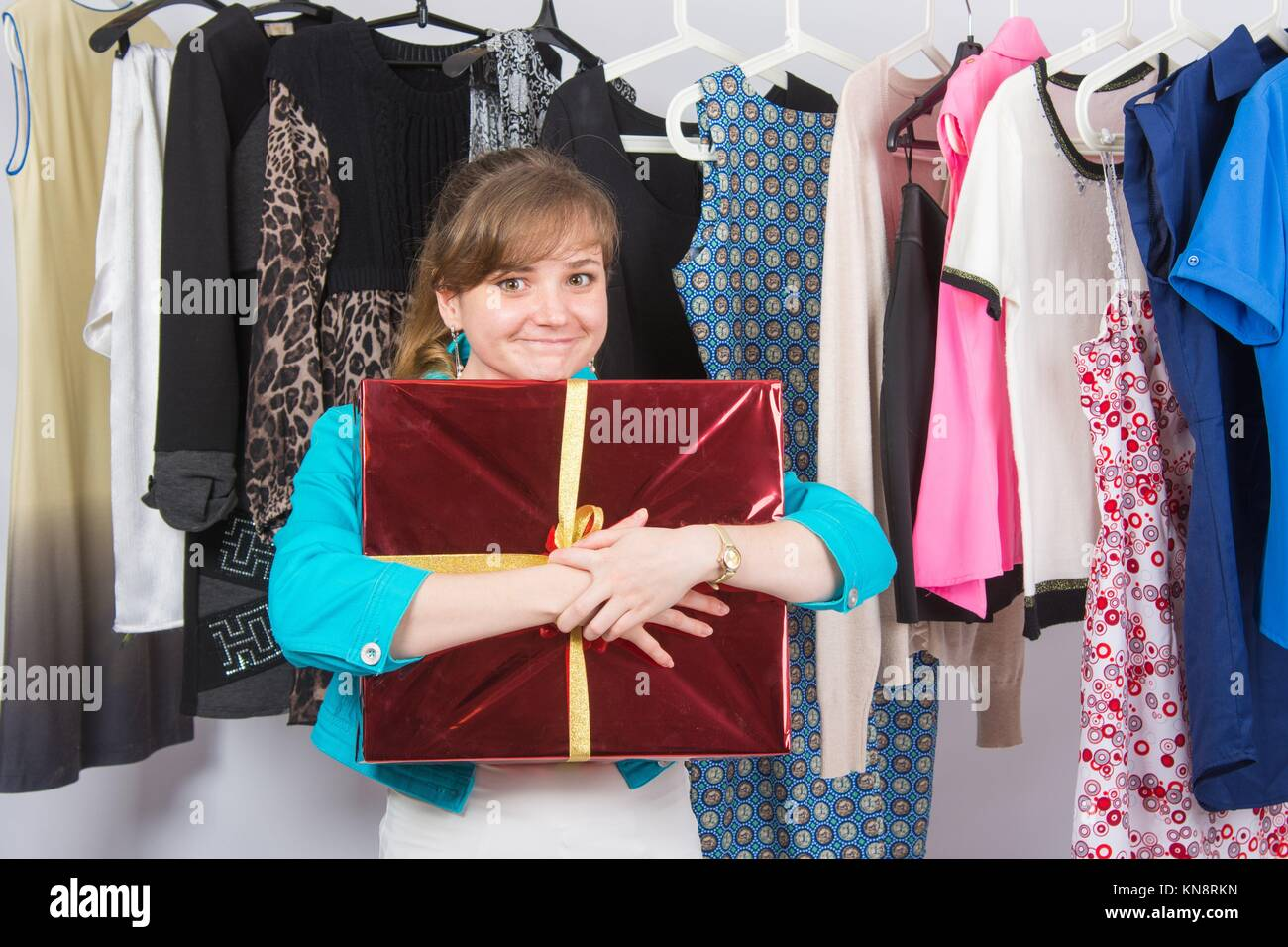 Happy young girl has received a welcome gift in the background hang things on hangers. - Stock Image