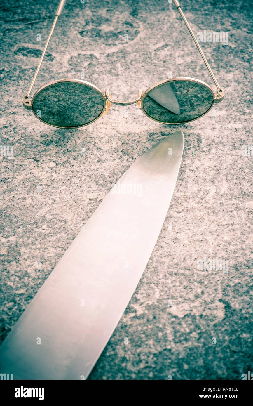 Round sunglasses and big knife on stone table, Retro eyewear. Concept of mystery, danger and fear. - Stock Image