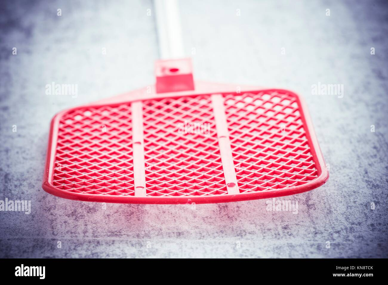 Fly swatter on stone table. Concept of exterminating bugs and insects. - Stock Image
