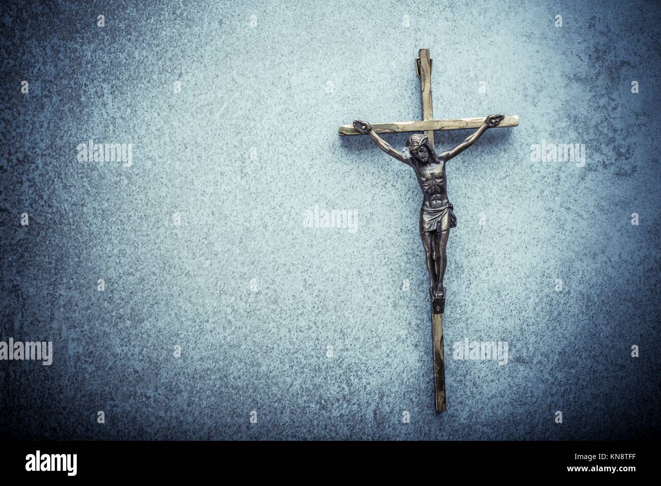 Crucifix of Jesus on the cross with stone background. Symbol of christian religion and belief. Image composed with - Stock Image