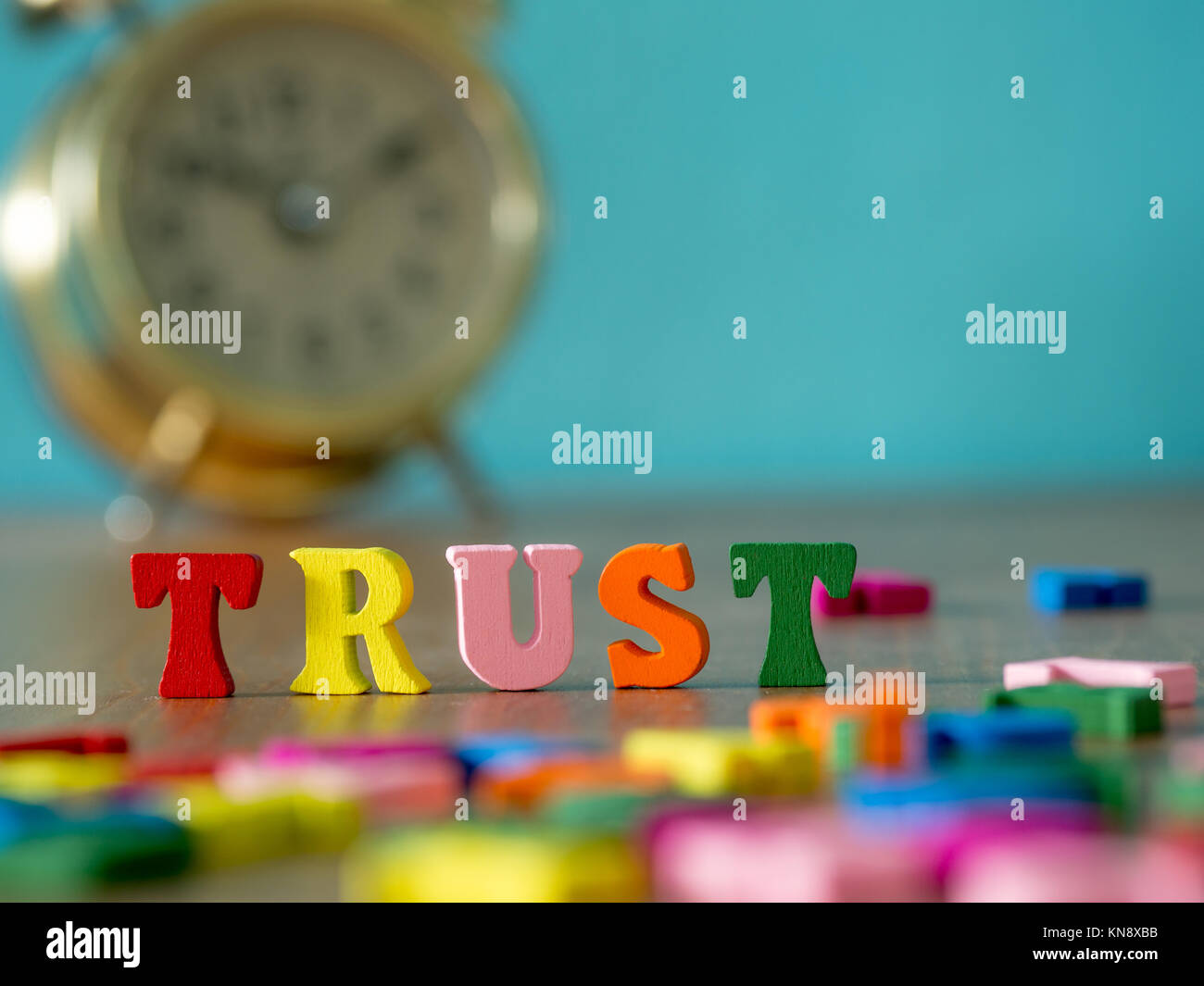 Trust. English alphabet made of wooden letter color. Alphabet trust on wooden table and vintage alarm clock and Stock Photo