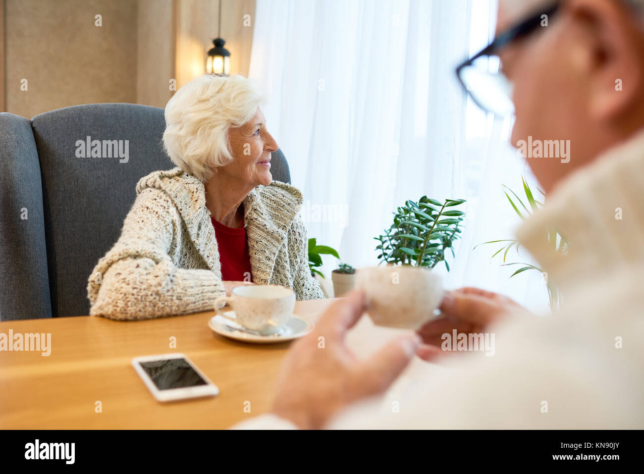 Pensive Senior Woman at Table in Cafe - Stock Image