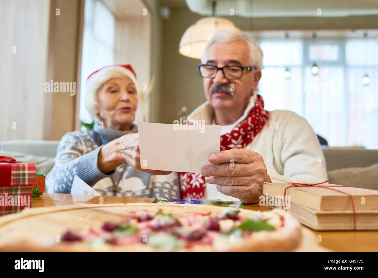 Senior Couple Looking at Family Photos - Stock Image