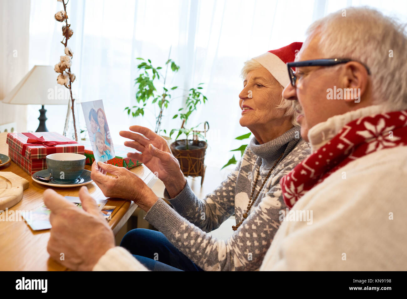 Senior Couple Looking at Photos  on Christmas - Stock Image