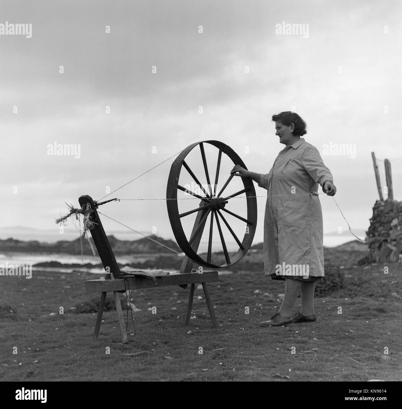 Photo of a woman spinning wool in Galway, in the Republic Of Ireland during the 1960s. The spinning machine is very - Stock Image