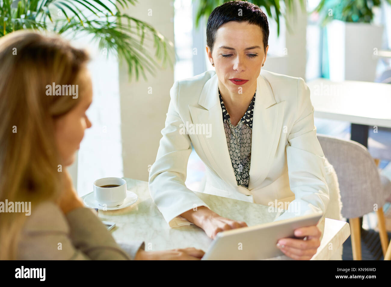 Successful Businesswoman Meeting with Partner in Cafe - Stock Image