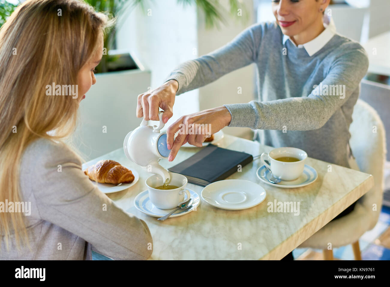 Two Young Women Enjoying Breakfast in Cafe - Stock Image