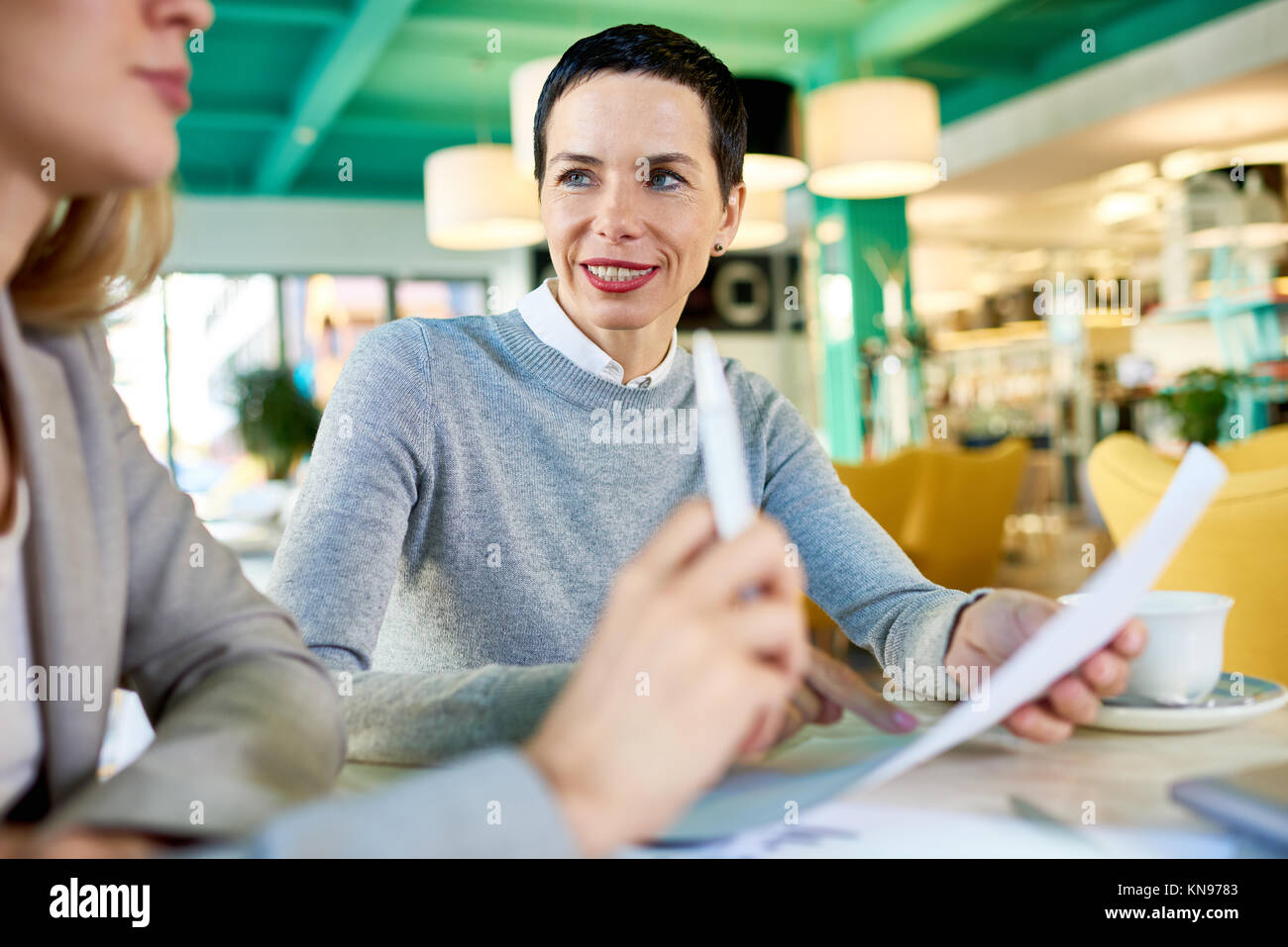 Mature Business Woman Leading meeting in Cafe - Stock Image