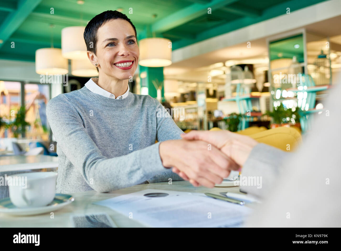 Businesswomen Shaking Hands in Cafe Meeting - Stock Image