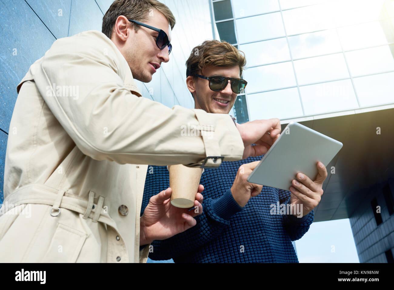 Two Men Using Tablet in Sunlight - Stock Image