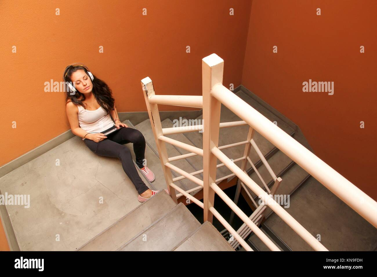 A young woman listening to melancholic Music sitting in the stairway. - Stock Image