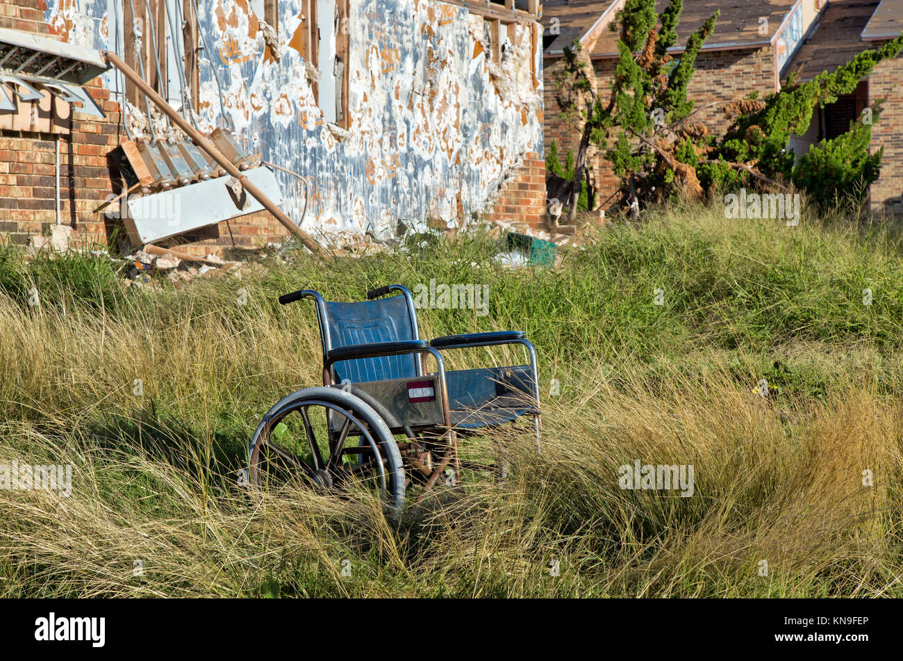 Abandoned wheelchair resting at destroyed housing complex, resulting from hurricane 'Harvey' 2017. - Stock Image