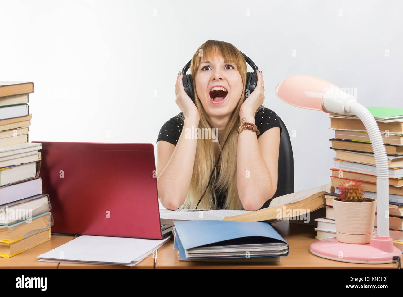 A student shouts from fatigue while listening to music on headphones. - Stock Image