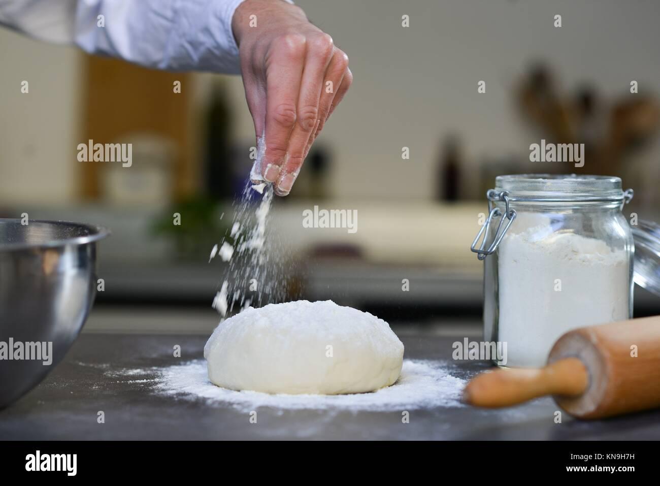 Chef preparing dough in kitchen flour douth Pizza. - Stock Image