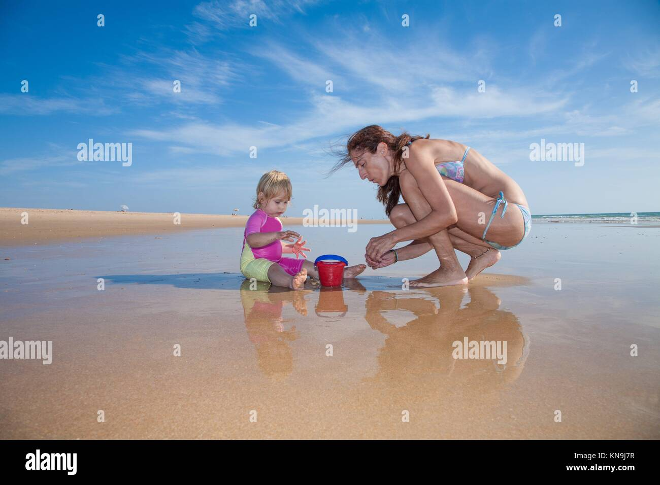 summer family of two years blonde baby pink and yellow swimsuit sitting on water with brunette woman mother in bikini - Stock Image