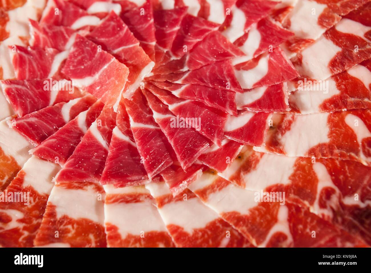 Circular decorative arrangement of iberian cured ham on plate. Selective focus point. Stock Photo