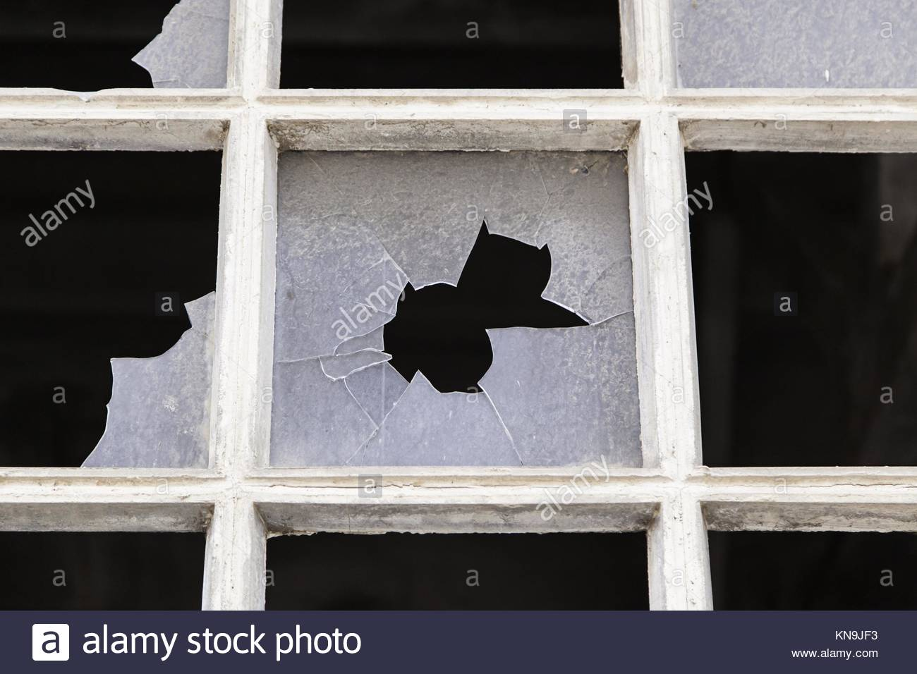 Old window with broken glass, detail of an abandoned factory, ruin and crime in Spain Stock Photo