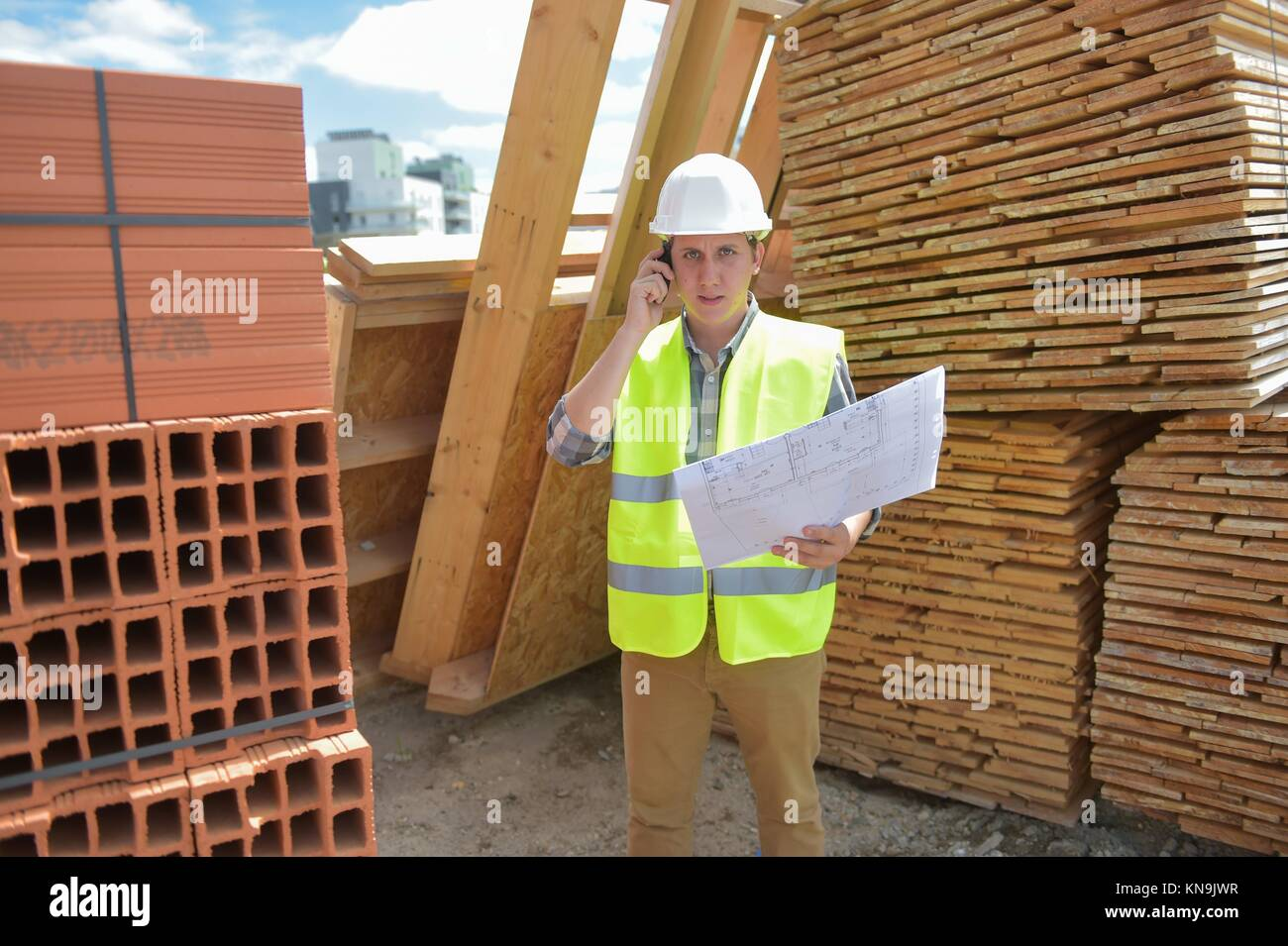 Foreman using walkie-talkie on construction site, France. - Stock Image