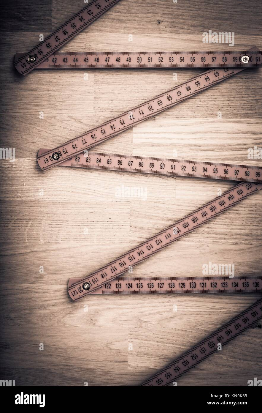 Folding rule on wooden table. Concept image of measurement, construction and work tool. - Stock Image