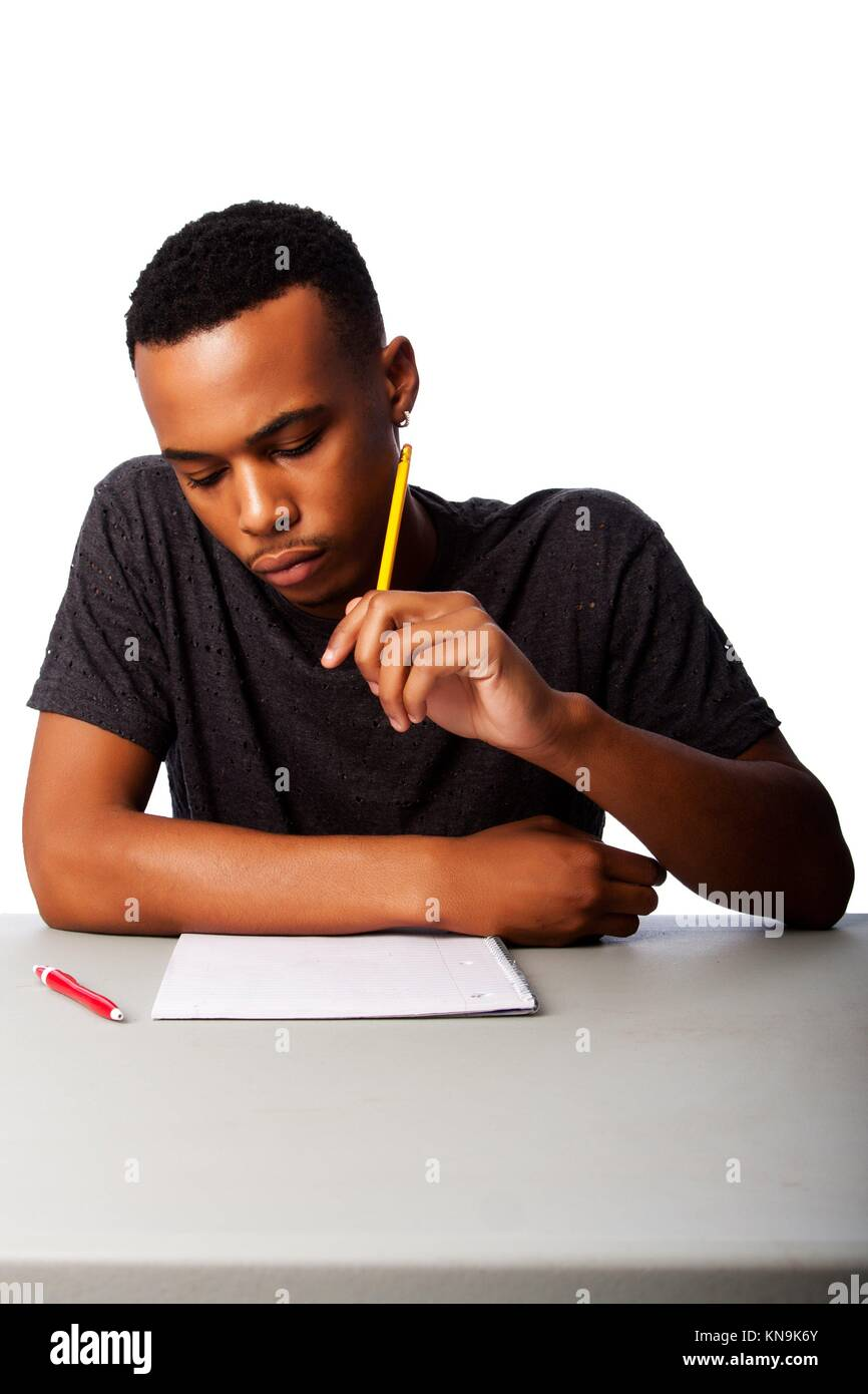 Handsome student thinking concentrating focussing for test examination sitting at desk, on white. - Stock Image
