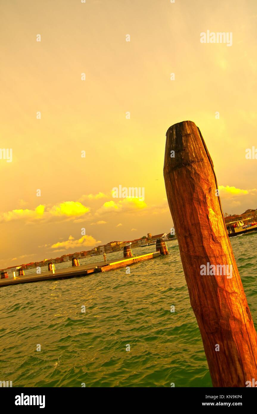 Venice Italy lagune view with ''bricole'' timber planted to sign the way of the canal. - Stock Image