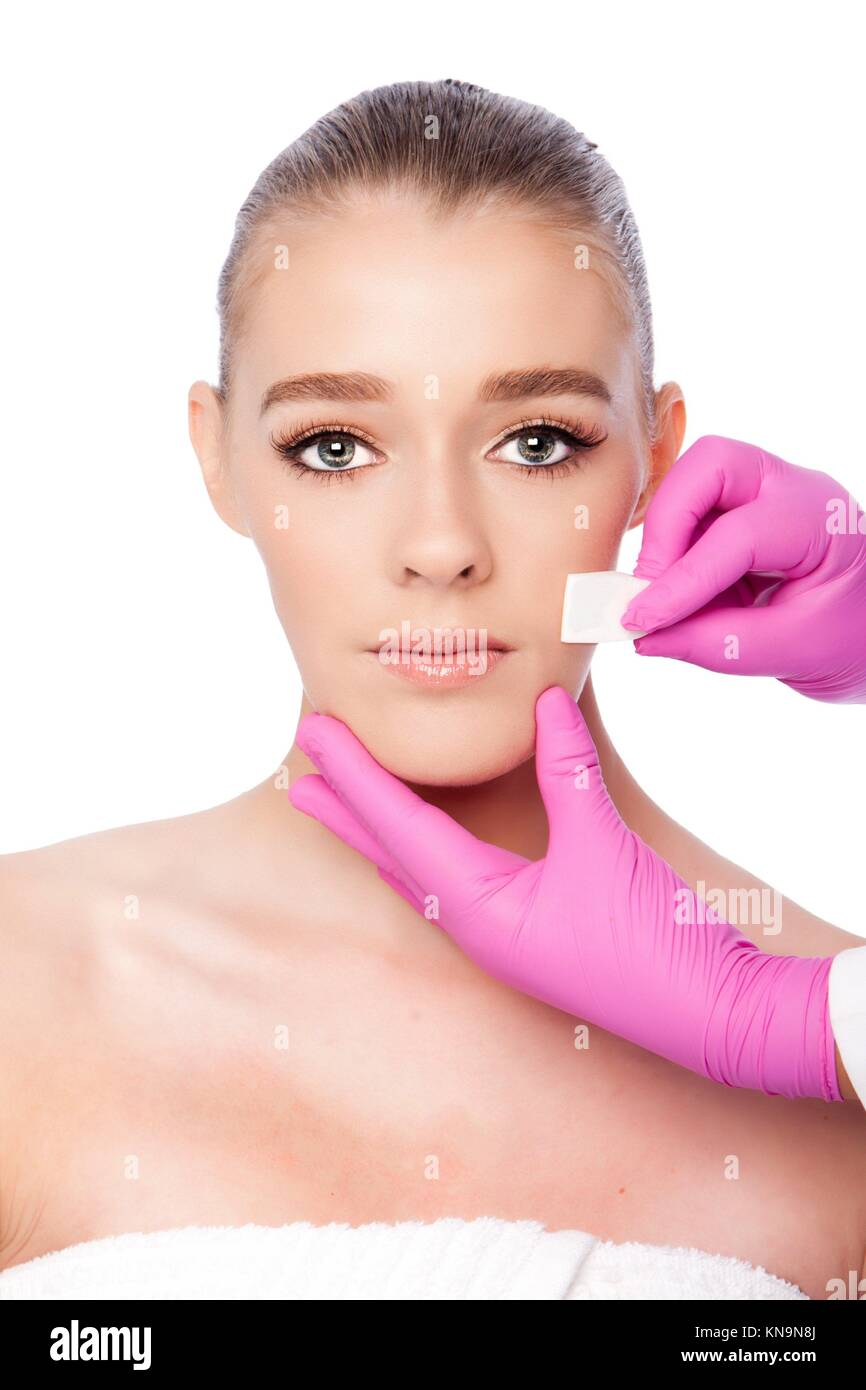 Beautiful face cleansing Cosmetic skincare spa beauty treatment with pink gloves and sponge, on white. - Stock Image