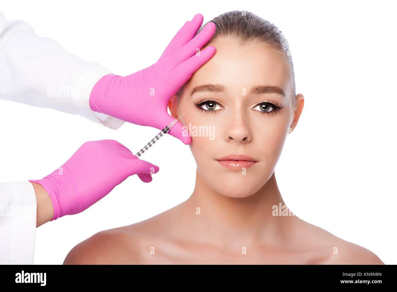 Beautiful face crows feet injection Cosmetic skincare spa beauty treatment with pink gloves by eye, on white. - Stock Image