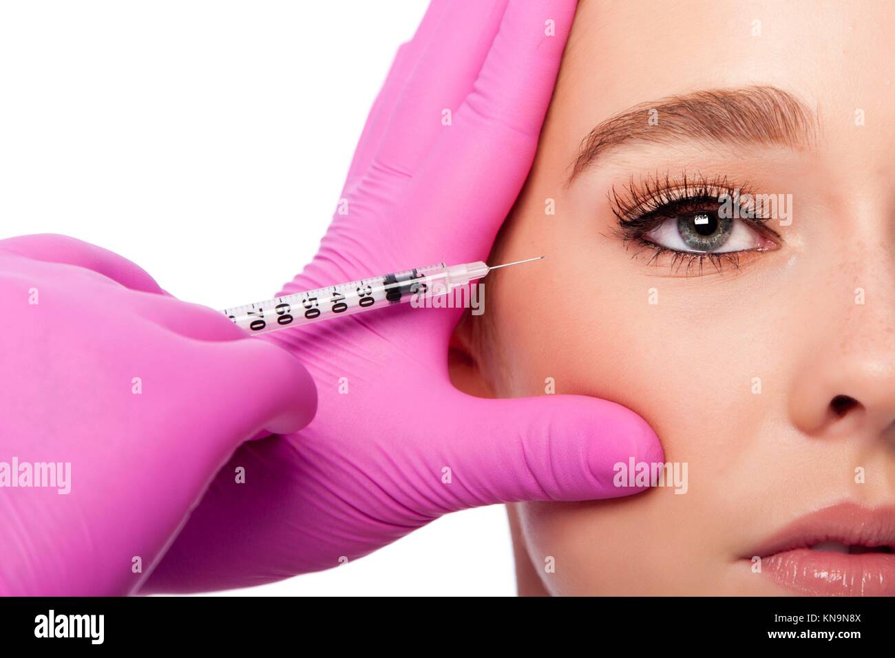 Beautiful face crows feet collagen filler injection Cosmetic skincare spa beauty treatment with pink gloves by eye, - Stock Image