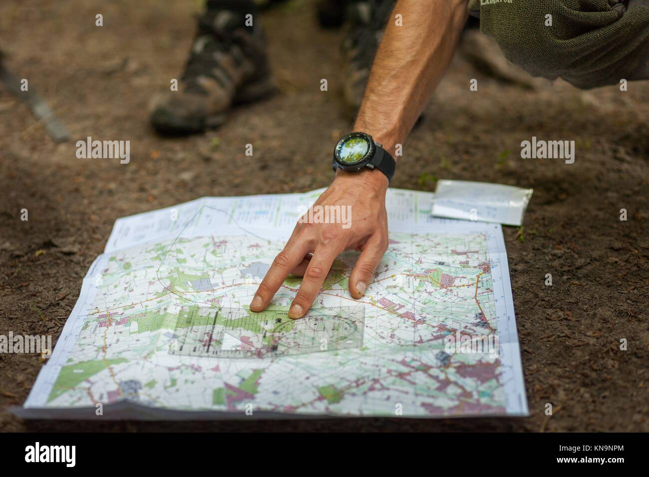 A group of hikers uses map and compass to navigate through the forest. - Stock Image