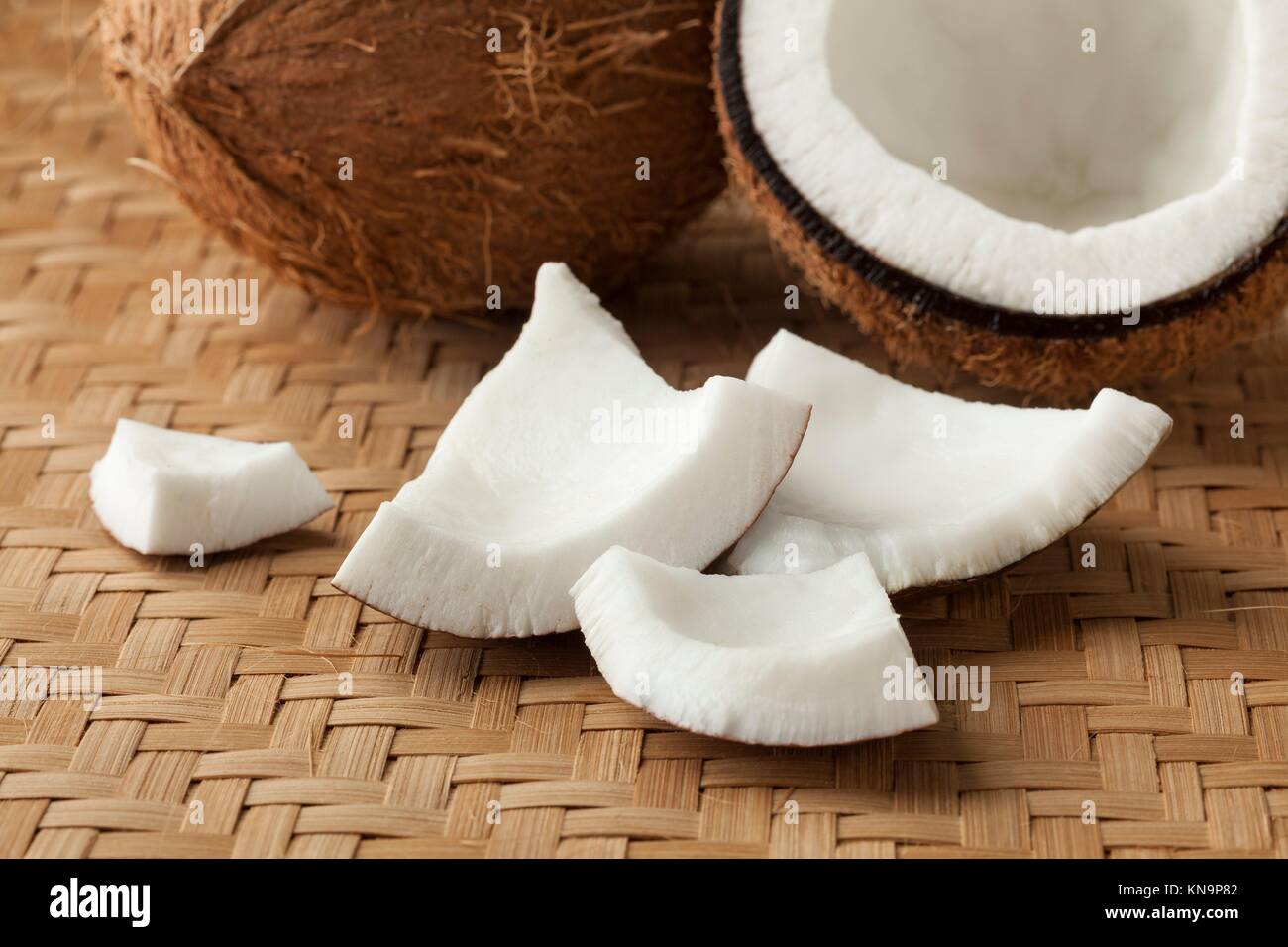 Cracked fresh coconut with pieces. - Stock Image