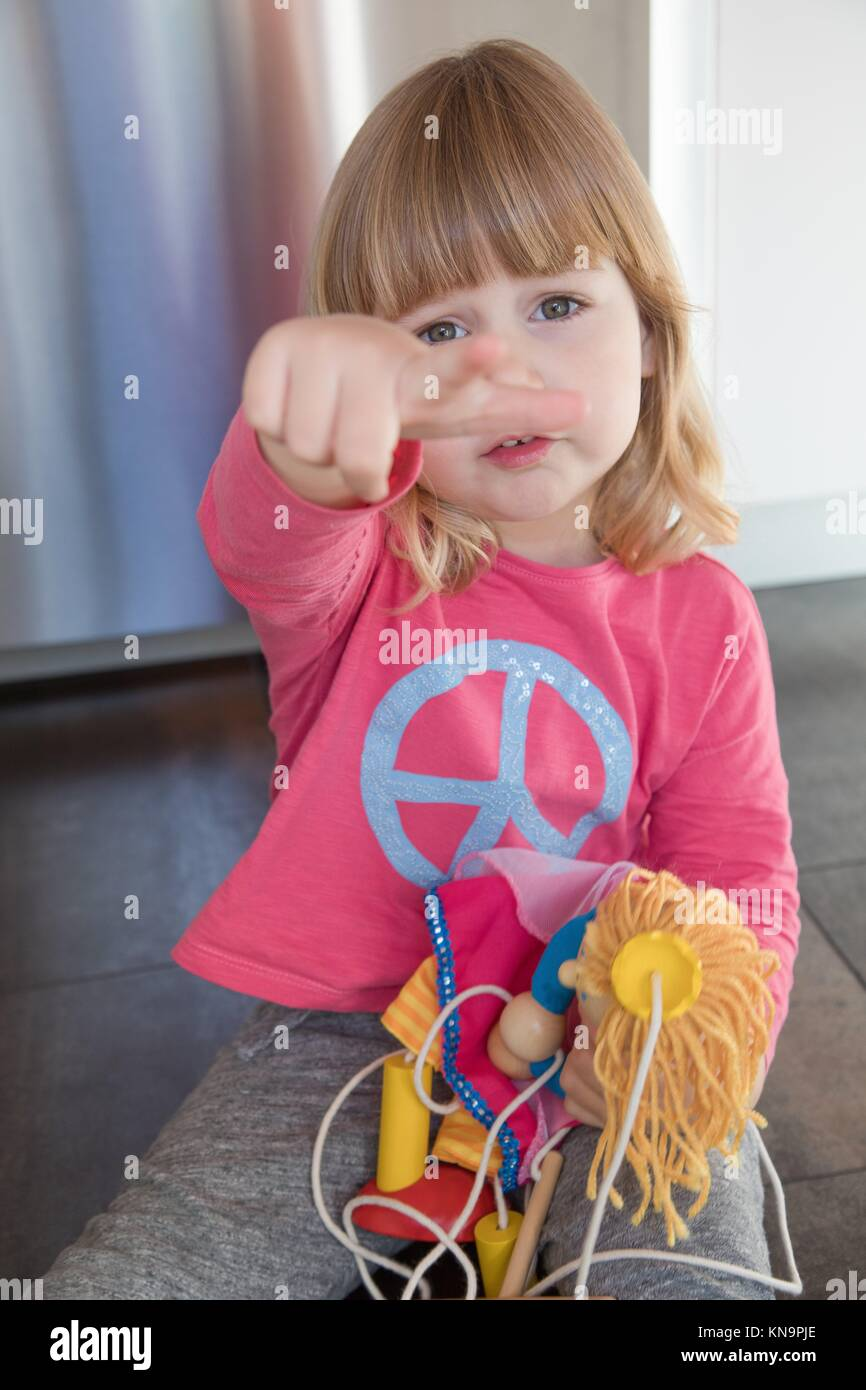 portrait of blonde three years old child with pink shirt blue peace hippie symbol, sitting on floor kitchen, annoying - Stock Image