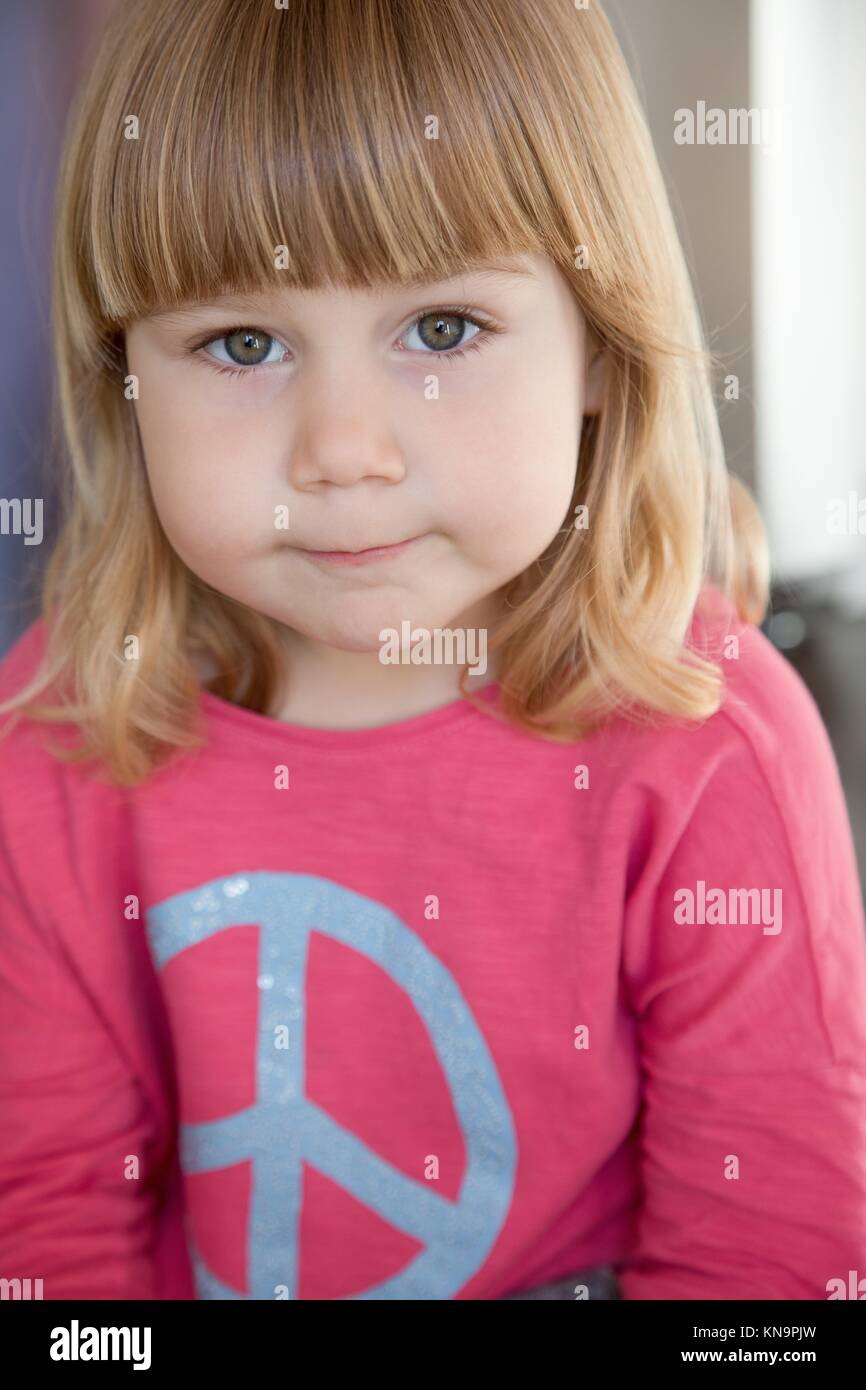 Portrait of three years old child face, blonde bang, with pink shirt blue peace hippie symbol, looking at camera - Stock Image