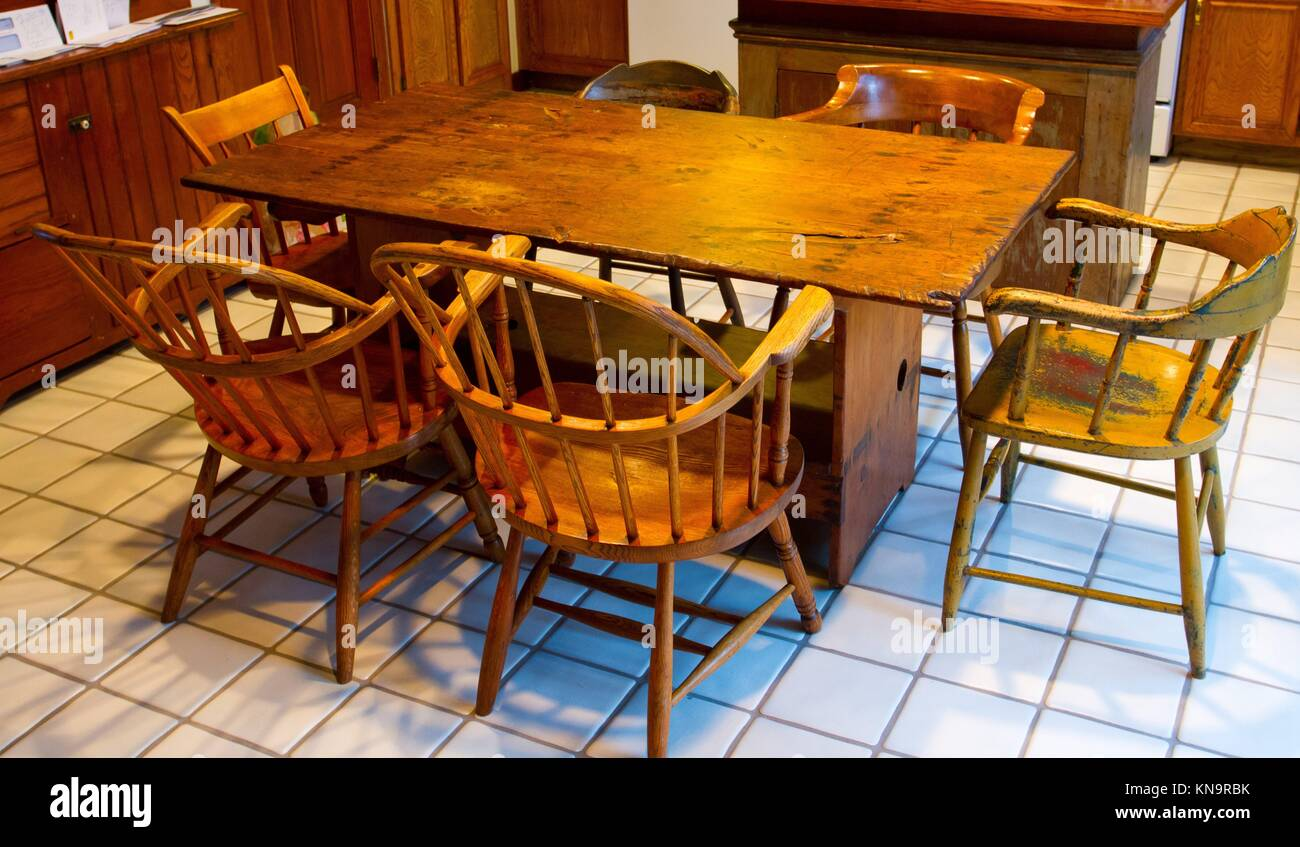 A Very Old Antique Dining Set With A Table And Chairs In A Kitchen.