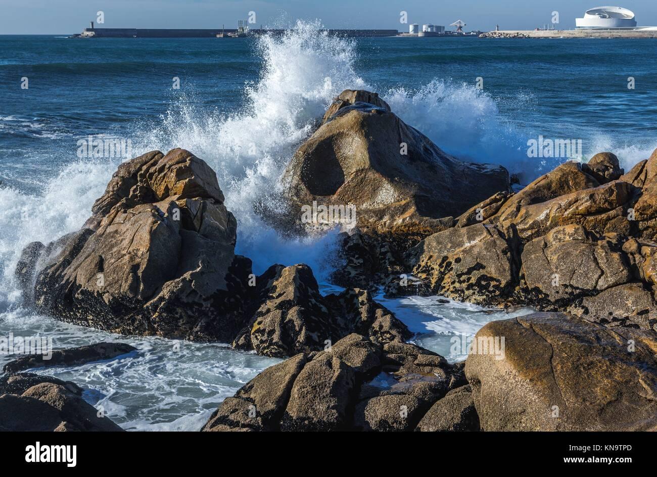 Waves smashing against rocks on the beach in Nevogilde civil parish of Porto, Portugal. Port of Leixoes Cruise Terminal - Stock Image
