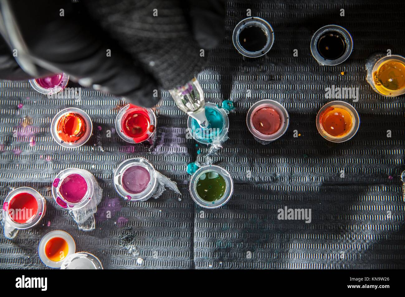 Tattoo artist refilling the pen with blue ink. Overhead shot. - Stock Image