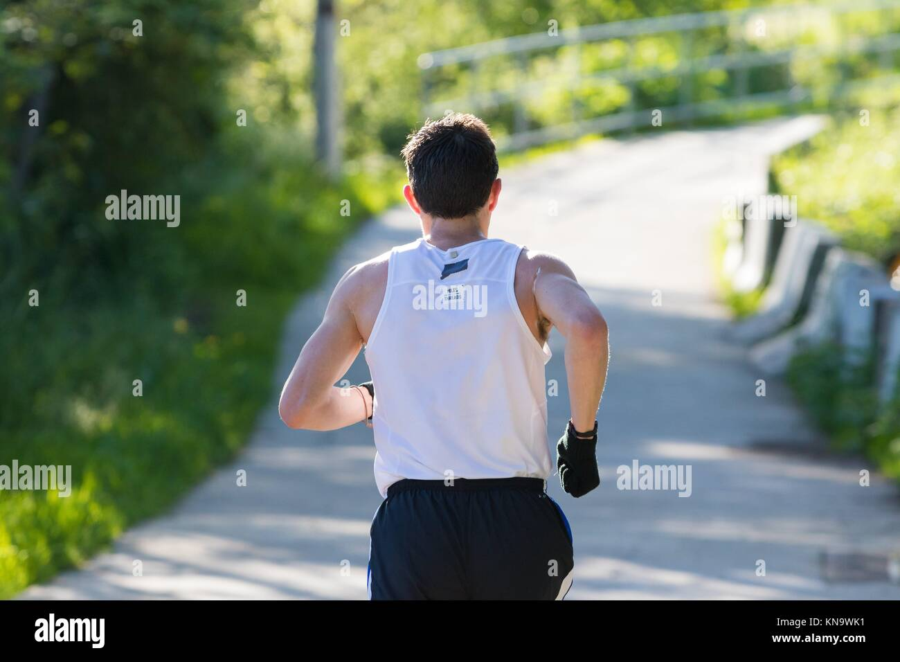 EUGENE, OR - MAY 7, 2017: Runner heads down the river path at mile 10 of the 2017 Eugene Marathon race held on the - Stock Image