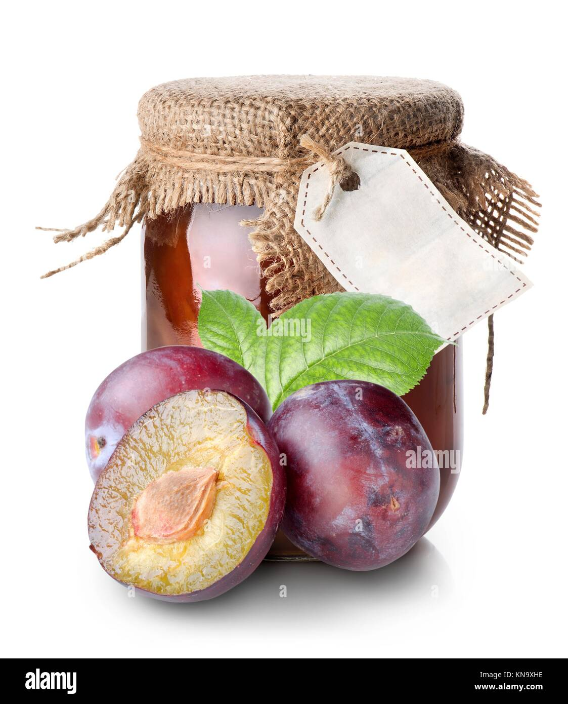 Plums and confiture in a jar isolated on white. - Stock Image