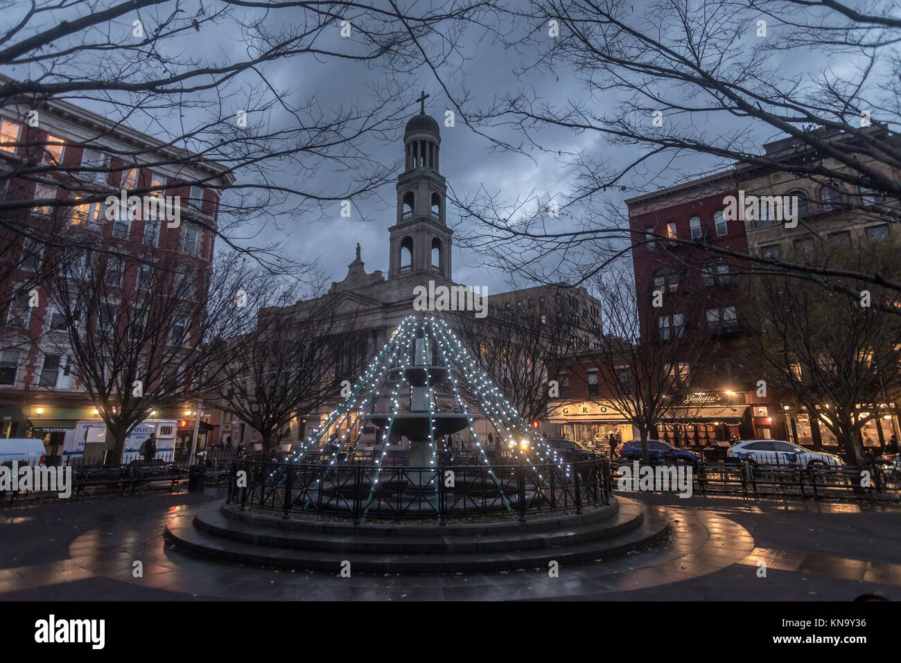 New York, NY, USA, Christmas lights on the fountain in Father Demo Square with Our Lady of Pompeii Catholic Church - Stock Image