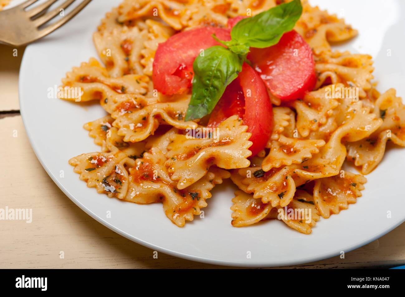 Italian pasta farfalle butterfly bow-tie with tomato basil sauce over white rustic wood table. - Stock Image