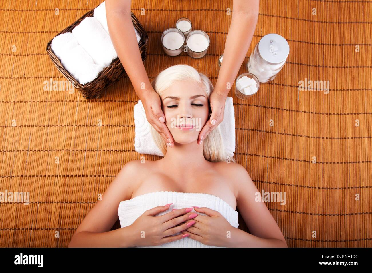 Beautiful young woman relaxing at spa getting therapeutic pampering facial massage, laying on bamboo. - Stock Image