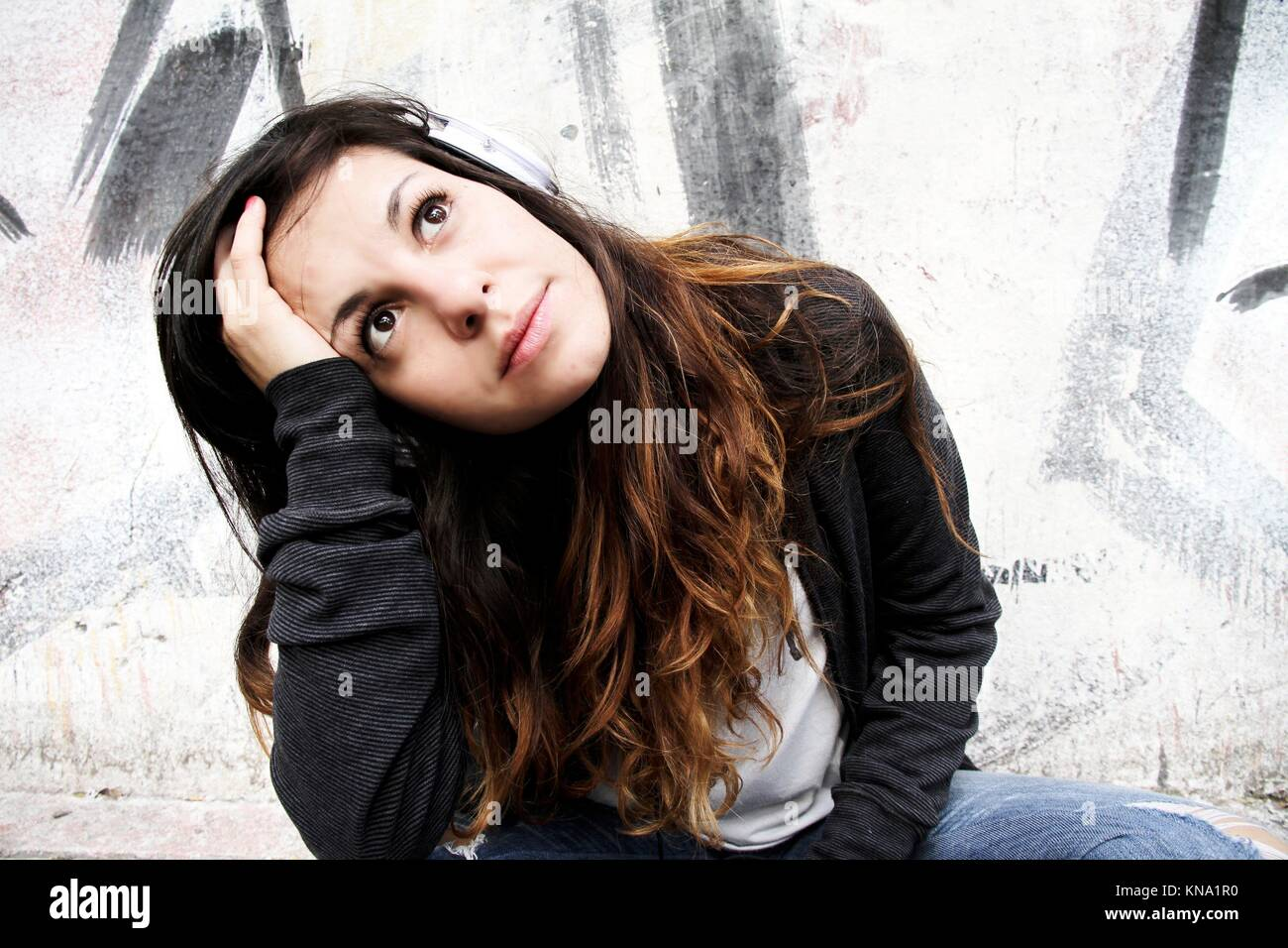 A young woman listening to melancholic Music and sitting on the pavement. - Stock Image