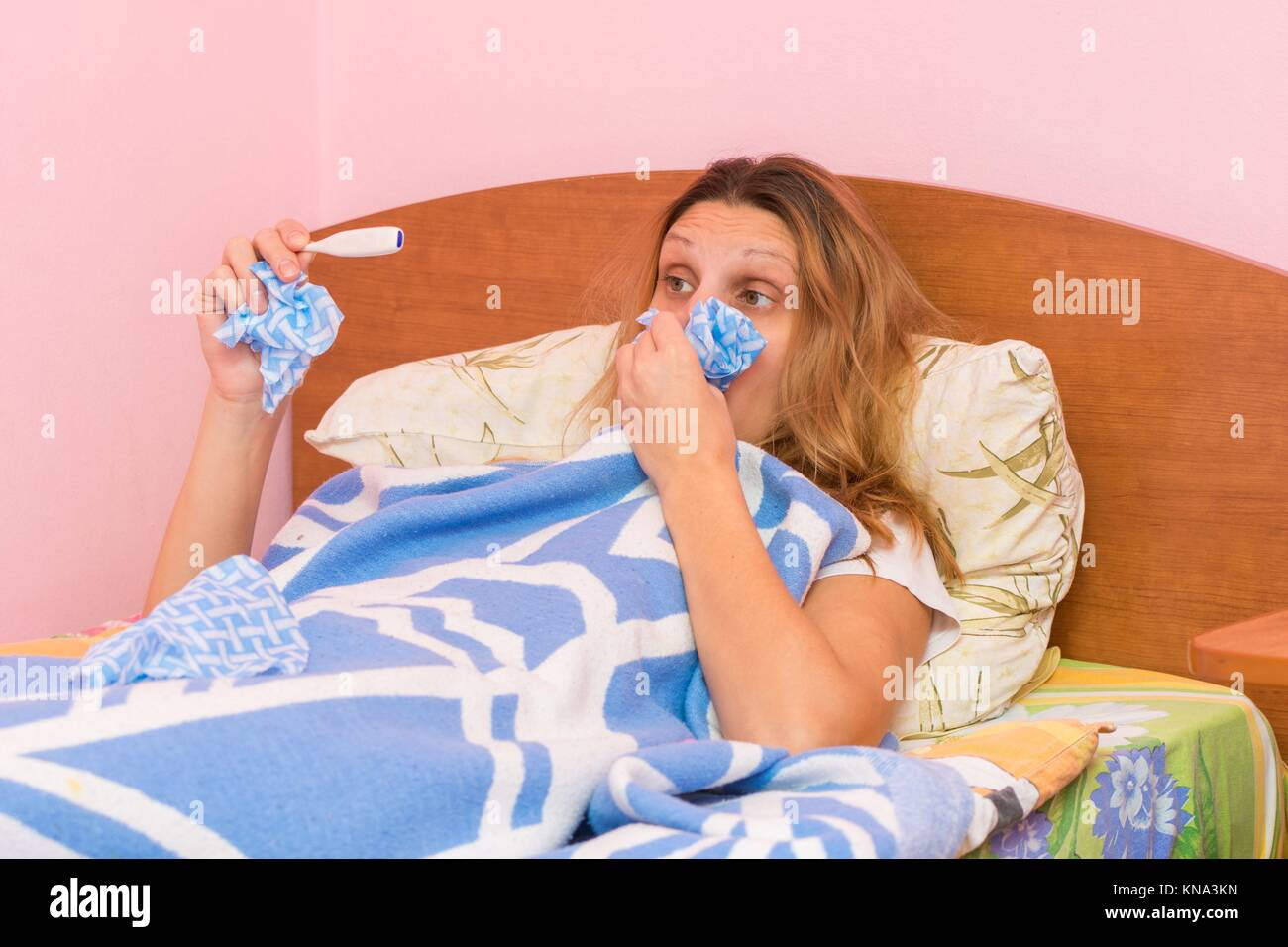 Diseased girl blows her nose into a handkerchief and looks at the thermometer. - Stock Image