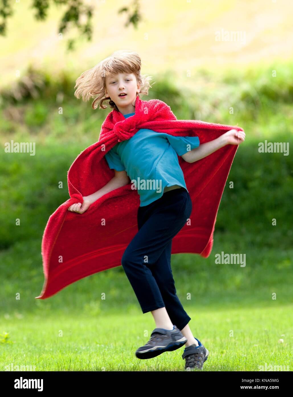 Boy Running Around in Red Towel as Superhero Cloak. - Stock Image