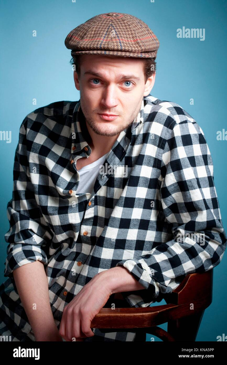 Portrait of a Young Man in a Checker Shirt and Cap. Stock Photo