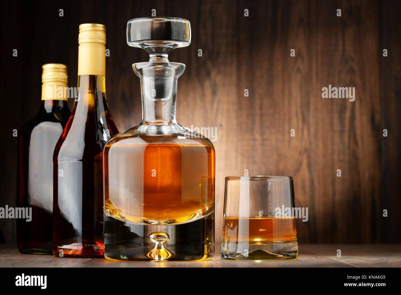 Composition with bottles of assorted alcoholic beverages and glass of whisky. - Stock Image