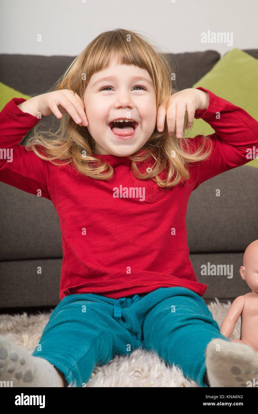 funny portrait of three years old child, with red and green clothes, looking, laughing and teasing with hands in - Stock Image