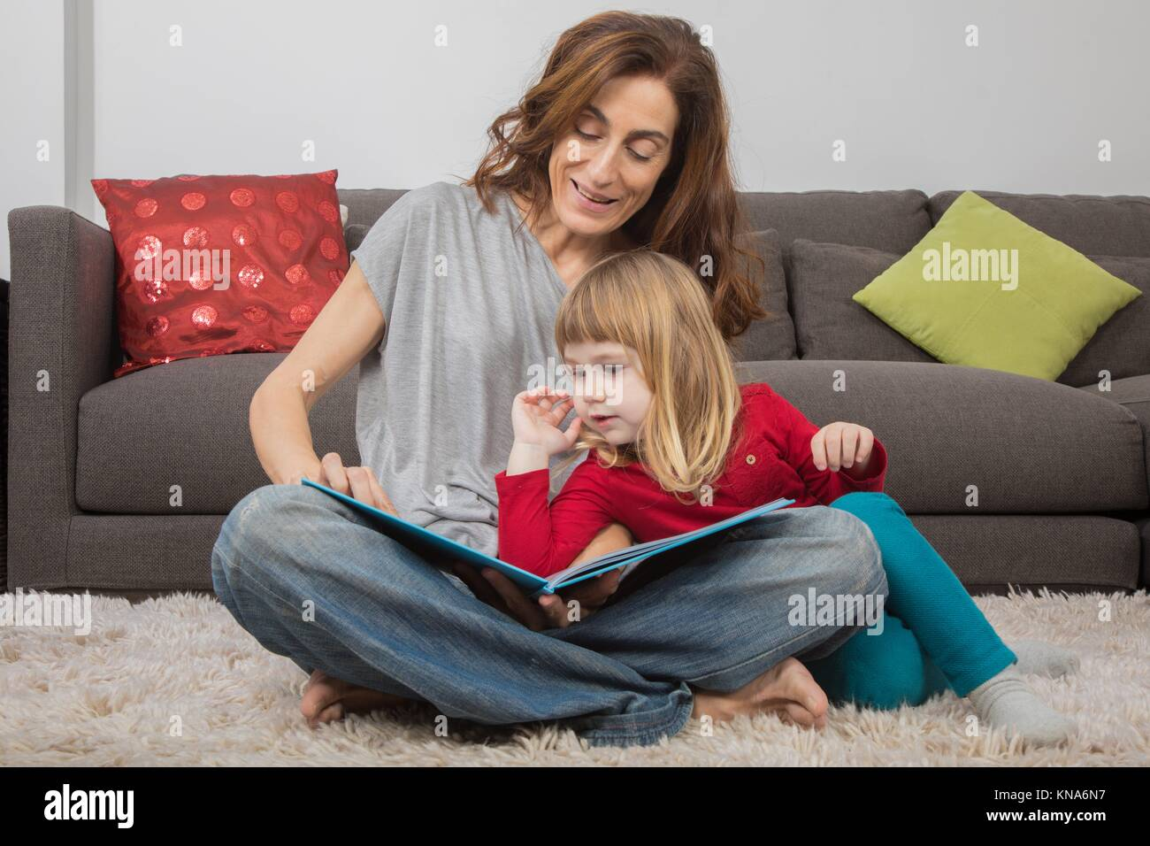 blonde child three years old, with red and green clothes, leaning on mother woman in jeans, reading together a story - Stock Image