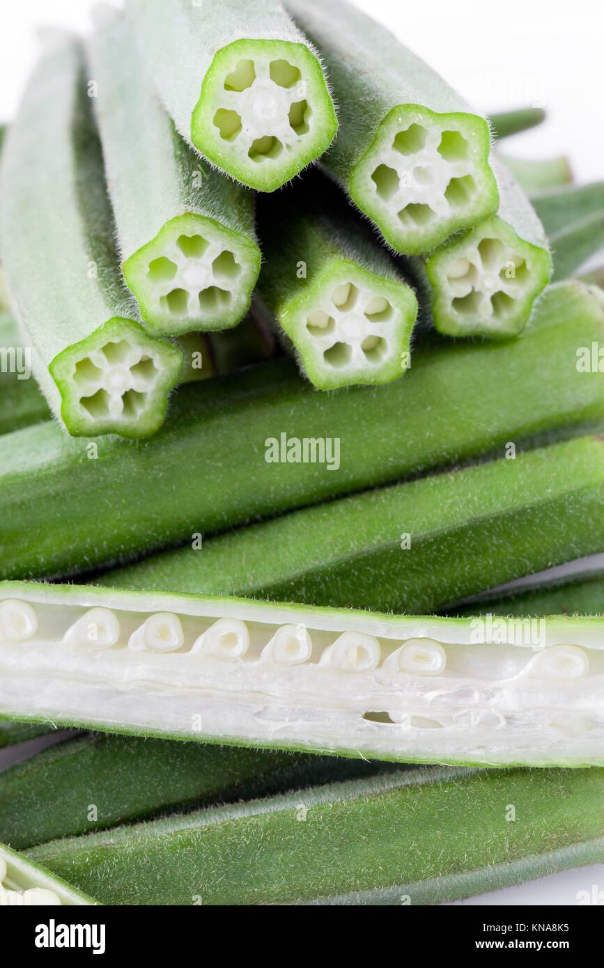 Okra pods with cut stem, whole and sectioned, vertical layout. - Stock Image