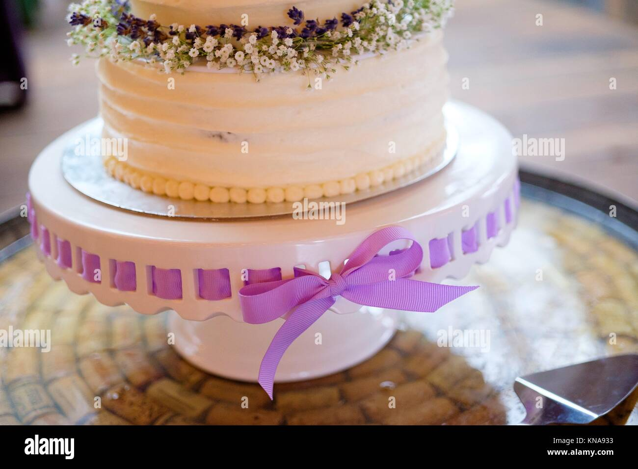 White wedding cake with a lavendar ribbon on a cakestand at a reception. - Stock Image