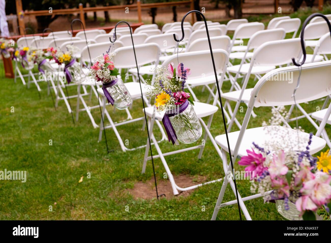 Ceremony Seating With White Chairs And Flowers At An Outdoor Wedding Stock Photo Alamy